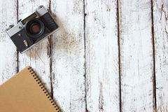Top view image of blank notebook, cup of coffee and old camera. Royalty Free Stock Images