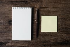 Top view image of blank notebook ,empty sticky note paper and pe. N on the wooden table stock photos