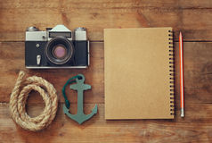 Top view image of blank notebook, nautical rope, anchor and camera. travel and adventure concept. retro filtered image Royalty Free Stock Photo