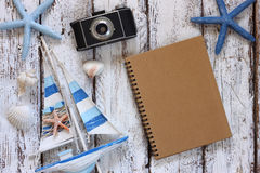 Top view image of blank notebook, wooden sailboat, starfish, shells and camera. travel and adventure concept Royalty Free Stock Photo