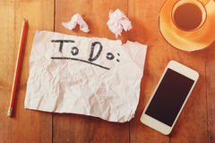 Top view image of blank paper with the text to do in hand write, next to cellphone and coffee cup over wooden table Royalty Free Stock Photo