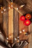 Top view image with bulblight garland, glowing candles and sackcloth bag on raw rustic background. stock images