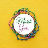 Top view image of colorful beads with text MARDI GRAS. Flat lay. Top view image of colorful beads with text MARDI GRAS. Flat lay
