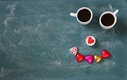 Top view image of colorful heart shape chocolates and couple mugs of coffee on blackboard background. valentine's day celebration Royalty Free Stock Photo