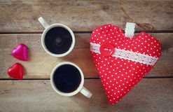 Top view image of colorful heart shape chocolates, fabric heart and couple mugs of coffee on wooden table Stock Photo