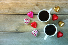 Top view image of colorful heart shape chocolates, fabric heart and couple mugs of coffee on wooden table Royalty Free Stock Image
