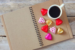 Top view image of colorful heart shape chocolates next to cup of coffee on open blank notebook on wooden table Royalty Free Stock Image