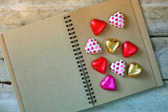 Top view image of colorful heart shape chocolates on open blank notebook on wooden table. valentine's day celebration concept Royalty Free Stock Photography