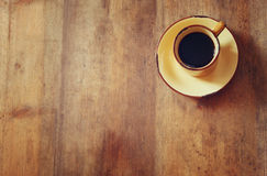Top view image of cup of black coffee over wooden textured table background. room for text Stock Images