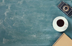 Top view image of  cup of coffee, notebook and vintage camera over blackboard background Royalty Free Stock Photography