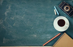 Top view image of cup of coffee, notebook and vintage camera over blackboard background Royalty Free Stock Photo