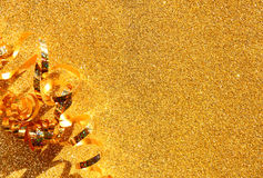 Top view image of curly golden ribbon over textured glitter background. Stock Images