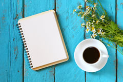 Top view image of daisy flowers, blank notebook next to cup of coffee on blue wooden table. Royalty Free Stock Images