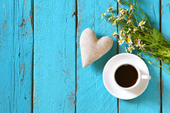 Top view image of daisy flowers and fabric heart next to cup of coffee on blue wooden table Royalty Free Stock Photography