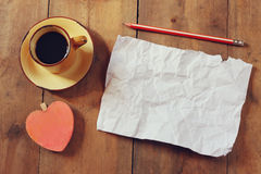 Top view image of empty crumpled paper, coffee cup and heart shape over wooden table Stock Photography