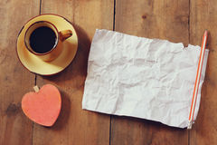 Top view image of empty crumpled paper, coffee cup and heart shape over wooden table Stock Photo