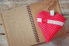 Top view image of fabric heart and open blank notebook on wooden table. valentine's day celebration concept. Stock Images
