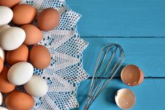 Farm Fresh Organic Eggs. A top view image of farm fresh organic eggs and wire whisk on a bright blue background stock photography