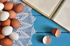 Farm Fresh Organic Eggs. A top view image of farm fresh organic eggs, wire whisk and cookbook on a bright blue background royalty free stock image