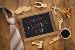 Top view image of fathers day composition with wooden shape tools, necktie , cup of coffee and blackboard Stock Images