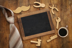 Top view image of fathers day composition with wooden shape tools, necktie , cup of coffee and blackboard Stock Photography