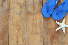 Top view image of flip flops and starfish. On wooden deck. vintage filtered. copy space royalty free stock images