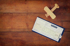 Top view image of flying ticket wooden airplane over wooden table Royalty Free Stock Image