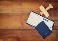 Top view image of flying ticket wooden airplane and passport over wooden table Stock Photography