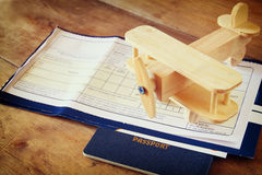 Top view image of flying ticket wooden airplane and passport over wooden table Stock Images