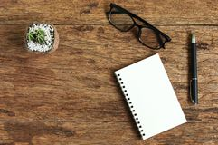 Top view image glasses of open notebook with pen on wooden table Royalty Free Stock Photos