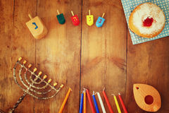 Top view image of jewish holiday Hanukkah with menorah (traditional Candelabra), donuts and wooden dreidels (spinning top)
