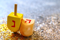Top view Image of jewish holiday Hanukkah. Image of jewish holiday Hanukkah with wooden dreidel & x28;spinning top& x29; on the glitter background
