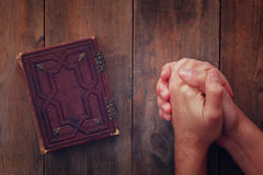 Top view image of mans hands folded in prayer next to prayer book. concept for religion, spirituality and faith.  Royalty Free Stock Photo