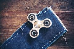 Top view image of a metal silver color fidget spinner on jean cloth with wooden table. Background Stock Images