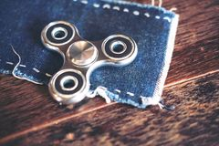 Top view image of a metal silver color fidget spinner on jean cloth with wooden table. Background Royalty Free Stock Images