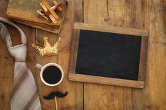 Top view image of old books, toy plane, glitter crown, necktie and cup of coffee next to blackboard Royalty Free Stock Photos