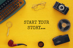 Top view image of old typewriter, camera, film and tape recorder. Over wooden yellow background. journalism or detective concept Royalty Free Stock Image