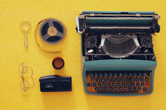 Top view image of old typewriter, film and tape recorder. Over wooden yellow background. journalism or detective concept Stock Photo