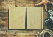 Top view image of open blank notebook, nautical rope, starfish and camera. travel and adventure concept. retro filtered image. Stock Image