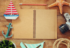 Top view image of open blank notebook, wooden sailboat, nautical ripe and camera. travel and adventure concept Stock Images
