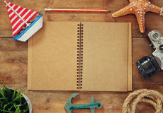 Top view image of open blank notebook, wooden sailboat, nautical rope and camera. travel and adventure concept Royalty Free Stock Image