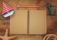 Top view image of open blank notebook, wooden sailboat, nautical rope. travel and adventure concept. retro filtered image Royalty Free Stock Photography