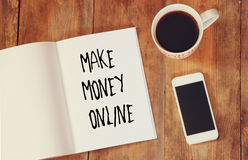 Top view image of open note book with the phrase make money online, next to cup of coffee and smartphone. Stock Photography