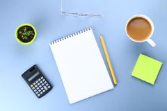 Top view image of open notebook with blank pages and coffee on blue background, ready for adding or mock up. Still life, business,. Office supplies or education Royalty Free Stock Photos