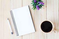 Top view image of open notebook with blank pages and coffee cup on wooden background, ready for adding or mock up Royalty Free Stock Photo