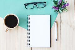 Top view image of open notebook with blank pages and coffee cup on wooden background, ready for adding or mock up Stock Photo