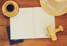 Top view image of open notebook with blank pages, cup of coffee wicker hat and wooden aeroplane over wooden table. ready for mocku Royalty Free Stock Photo
