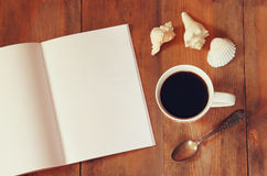 Top view image of open notebook with blank pages next to cup of coffe on wooden table. ready for adding text or mockup