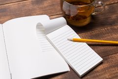 Top view image of open notebook with blank pages next to cup of coffee on wooden table. mockup. Top view image of open notebook with blank pages next to cup of stock images