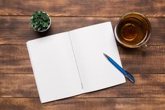 top view open notebook with blank pages next to cup of coffee on wooden table. ready for adding text or mockup stock images
